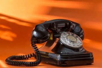 old black telephone, on orange background