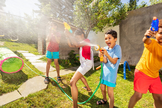 Very happy boy with sprinkler in water gun fight