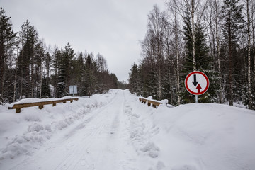 Oncoming traffic sign on a narrow winter road with a bridge in the forest