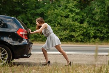 Woman pushing broken car on road, breakdown