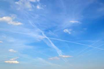 Jet trails in the sky with white translucent cirrus clouds. Many airplane contrails in a blue sky on a day.