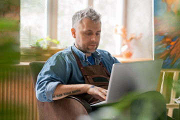 Serious painter in workwear sitting in studio in front of laptop display