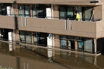 A man looks out from an apartment with the first floor flooded from heavy rains last night due to Typhoon Hagibis, near the Tama River in Kawasaki
