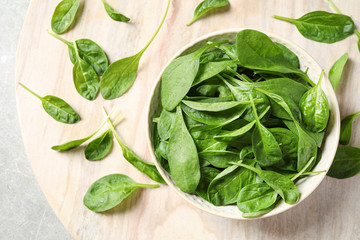 Bowl of fresh green healthy spinach on table, flat lay