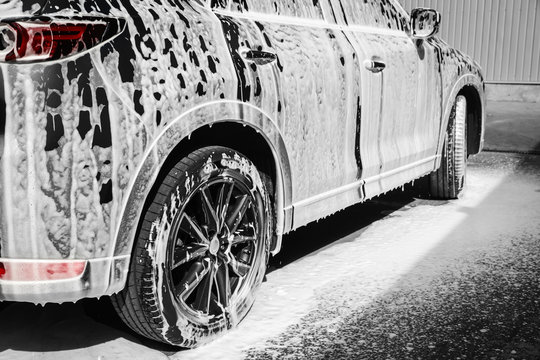 Luxury automobile covered with foam at car wash, closeup