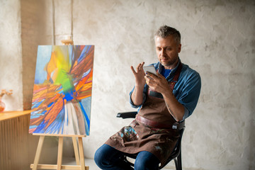 Serious middle aged painter in apron and casualwear scrolling in smartphone