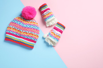 Warm knitted hat and mittens on color background, flat lay. Space for text
