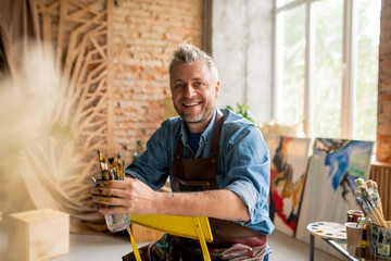 Cheerful artist in workwear sitting on chair in front of camera