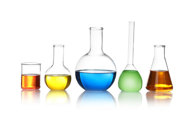 Fototapete - Laboratory glassware with color liquids on white background