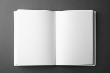 Open book with blank pages on dark grey background, top view. Mock up for design