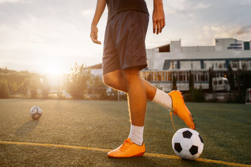Soccer player with ball on the field at sunrise