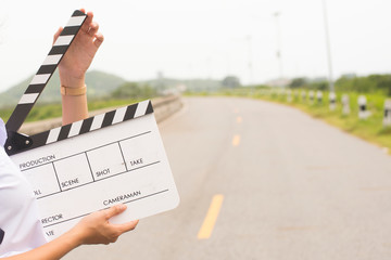 Girl holding a clapboard on road background.