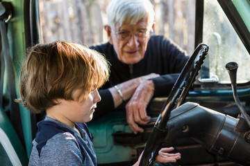 senior grandfather and his 6 year old grandson in vintage pick up truck