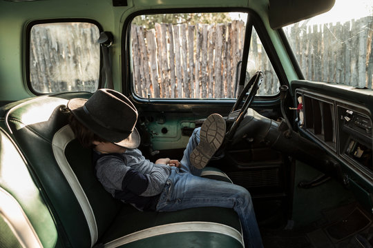 6 year old boy sitting in vintage pick up truck with hat covering his face