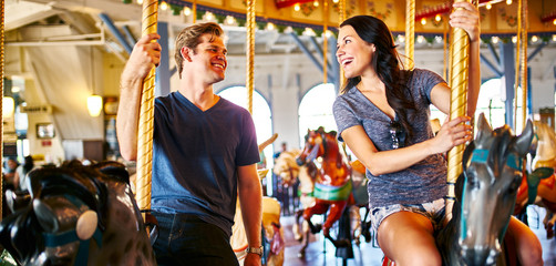 romantic couple riding carousel together on date
