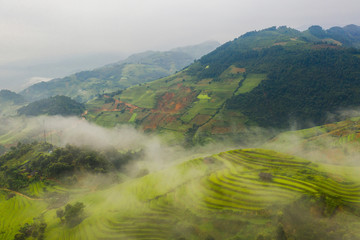 Foto op Plexiglas Guilin Aerial top view of paddy rice terraces, green agricultural fields in countryside or rural area of Mu Cang Chai, Yen Bai, mountain hills valley at sunset in Asia, Vietnam. Nature landscape background.