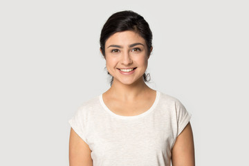 Headshot portrait of smiling indian girl posing in studio