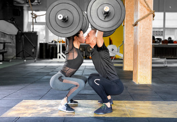 Fitness couple making a Barbell Jerk and kissing each other. Sporty family in gym.