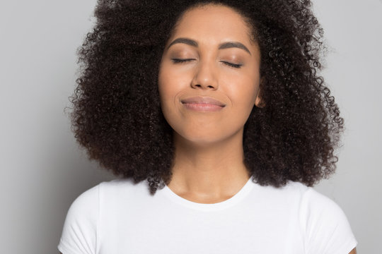 Happy african American girl with eyes closed relieve negativity