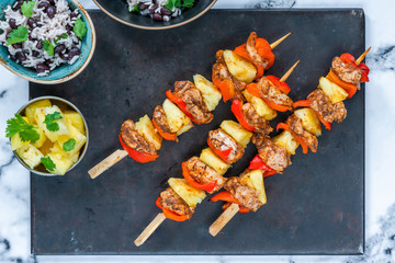 Jerk-style chicken and pineapple skewers with black bean rice - overhead view