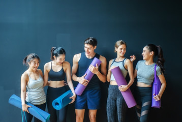 Group of young sporty people with fitness yoga exercise mats standing beside black wall.Students...
