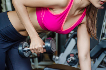 Close-up photo of Young beautiful woman doing exercises lifting dumbbell in gym. Girl is enjoying with her training process in the morning. She is working hard
