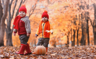 Children are walking in nature. Twilight kids are walking around the park. Brother with sister in autumn city park in leaf fall.