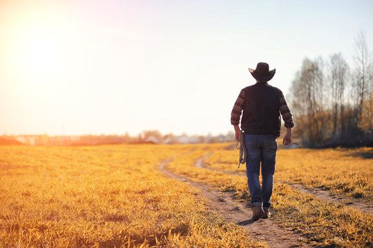 A man cowboy hat and a loso in the field. American farmer in a field wearing a jeans hat and with a loso. A man is walking across the field in a hat