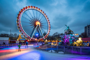Christmas market near the Neptune Fountain in Berlin with Ferris wheel and ice rink in winter