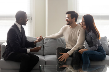 Happy young family couple listening to financial expert offer.