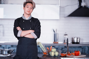 Asian cook in the kitchen prepares food in a cook suit