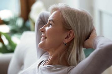 60s woman put hands behind head resting indoors enjoy weekend