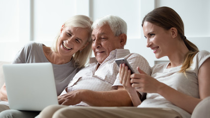 Three generations family with modern gadgets at home