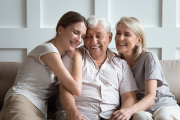 Cheerful three-generation family sitting on couch enjoy time together