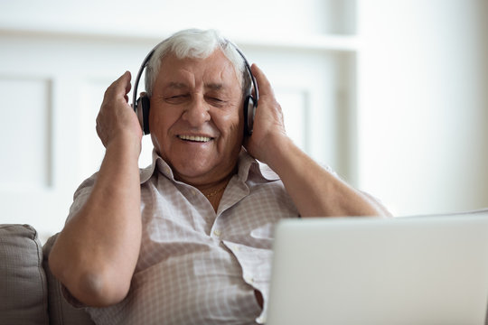 Senior man wearing headphones listens songs on laptop