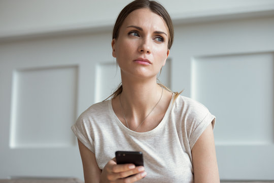 Sad woman holding smartphone waiting call from boyfriend feels jealousy