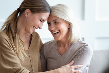 Closeup image aged mother and adult daughter touch foreheads laughing