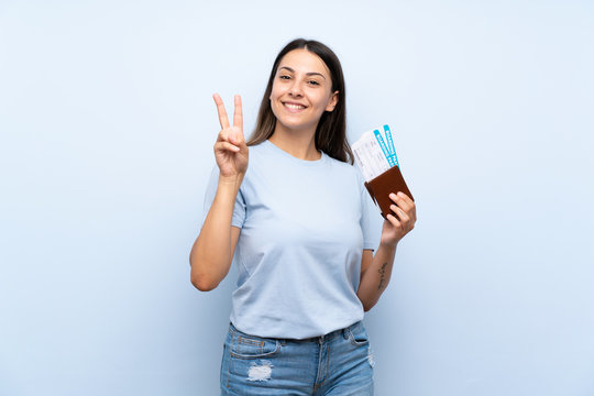 Traveler woman with boarding pass over isolated blue wall smiling and showing victory sign