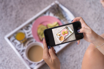 detail screen shot mobil phone of healthy breakfast on a tray with mobile phone. Young woman food blogger takes blog photo of coffee latte, orange juice and avocado fresh toasts. Horizontal photo.
