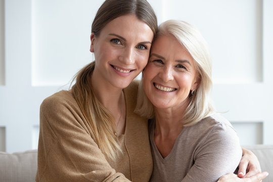 Attractive aged mother and adult daughter hugging looking at camera