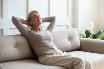 Older 50s female resting seated on couch with closed eyes