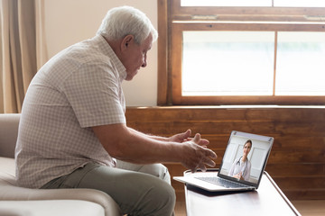 Elderly man make distant video call communicating with doctor online