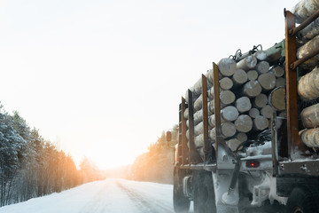 Truck with timber logs on a winter road