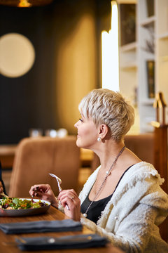 Beautiful caucasian woman 60 years old with a fork in hand sit in restaurant and attentively listen to person opposite. Elegant, attractive person in expensive place