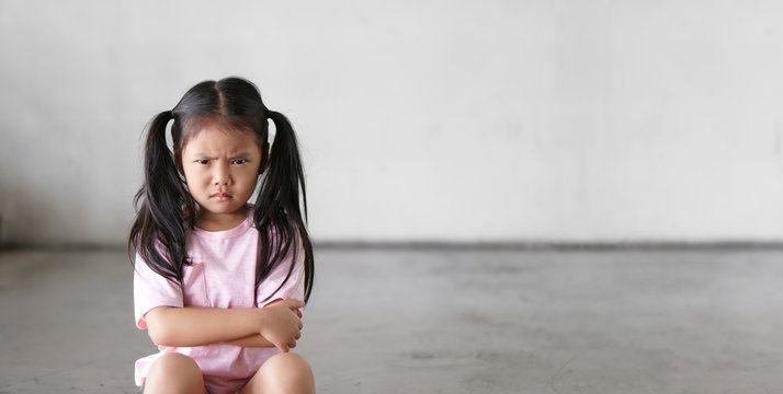 Asian child cute touchy or kid girl sitting face frown and angry aggressive with sad or have problems and lonely unhappy or wayward on city street and footpath at home or nursery and school with space