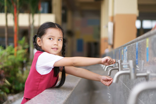 Asian child cute or kid girl and student smiling happy with wash hands on tap in sink on public at kindergarten school or preschool for dirty clean and bacteria or virus with wear school uniform