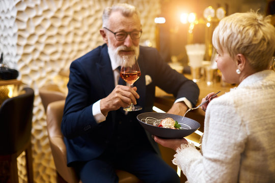 Mature couple of caucasian man and woman sit in restaurant and eat dessert, drink glass of wine. Male in tuxedo, female in white blazer. Woman holding dish