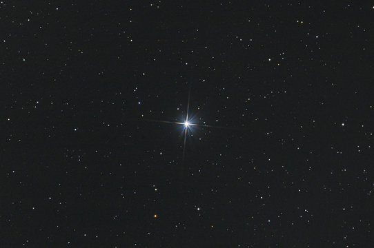 Closeup of the star Sadr in Cygnus constellation, with many stars as background in the deep space.