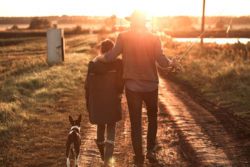 Father hugged son. They and dog walk along country road along lake to fishing spot. Sunset.