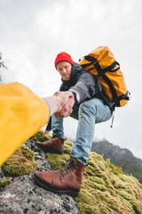 POV view on brave tourist helping his active friend holding to hand climbing to rock. Two travelers climb to mountains lifestyle outdoor vacation. Vertical